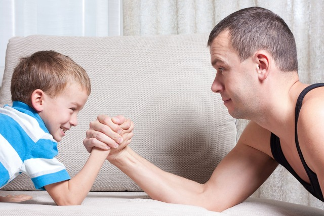 Father and young son are fighting, indoor